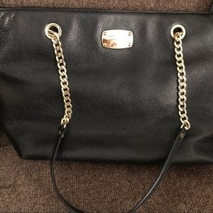 Michael Korrs black pebbled leather chain tote.